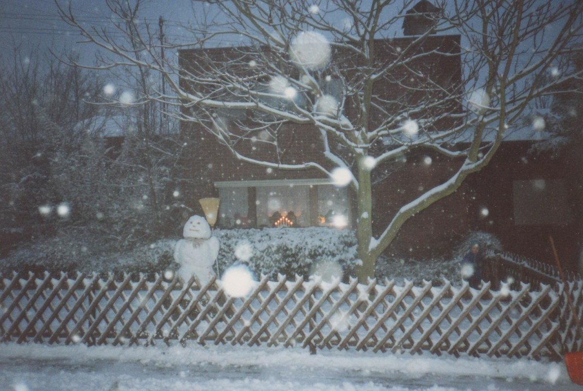 "Our ""snowperson"" stands watch in the front yard - always maintaining a smiling and happy disposition while watching the snow float down in large flakes - on a perfectly still and calm winter evening with David standing at the gate into the front yard."