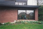 I was in the captain's group for our skit, and as we were an unimaginative bunch - it was determined that we would build a human pyramid with all the pilots in our group stacked up on all fours; in this picture David stands in the living room window with the spring tulips lining the flower bed behind our house in Monzelfeld.