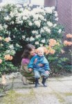 David's grandmother poses with him outside our home in Monzelfeld, in front of beautiful flowering bushes that look to be Azaleas, growing directly outside the sliding glass doors of the dining room.