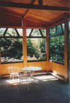 """This is what I call the """"hunter's lodge"""" style covered porch - huge and open to the forest on two sides with flower boxes on the outside of the knee walls; the unfortunate thing was that we never got the time to really grow into this part of the house and it often went unused."""