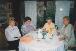 My wife's aunt, both grandmothers and her great-aunt share conversation and a photo album at our dining table in Monzelfeld, with my wife's handmade crochet curtains hanging in the windows of the sliding glass doors.