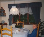 A picture of David at our dining room table on the 2nd Advent Sunday, with my wife's hand-crocheted lace curtain, lamp shade and trim on the hanging shelves.